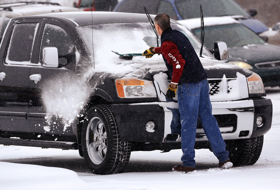 Photo - A man brushes snow from his car's windshield after Sunday services at Cornerstone Church in Midwest City. Snow began falling in central Oklahoma around 7 Sunday morning, Feb. 2, 2014.   Photo by Jim Beckel, The Oklahoman