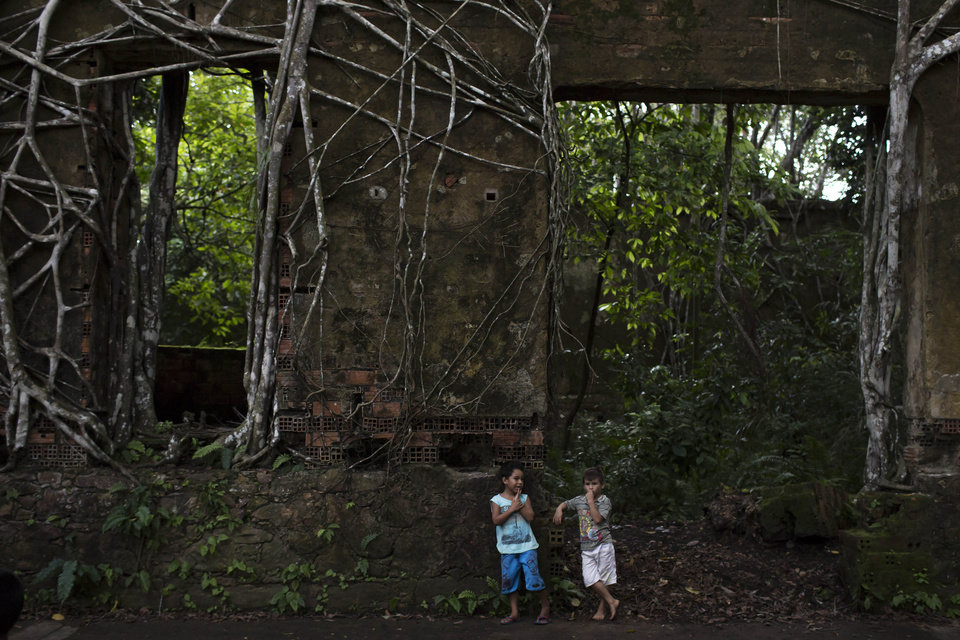 Photo - In this May 21, 2014 photo, boys rest after playing in the ruins of Paricatuba, near Manaus, Brazil. Darker things, too, are said to take place inside these crumbling walls. There's the room fitted out with rusting, vine-engulfed bars that once kept prisoners in check. There's a former bathroom with spooky red streaks along one of the walls and a straw broom leaning in the corner, left there, one of the kids suggested, by a witch. There's the spot where, legend has it, lepers' bodies were burned. (AP Photo/Felipe Dana)
