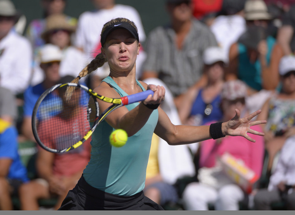 Photo - Eugenie Bouchard, of Canada, makes a return against Sara Errani, of Italy, during a match at the BNP Paribas Open tennis tournament on Sunday, March 9, 2014, in Indian Wells, Calif. (AP Photo/Mark J. Terrill)