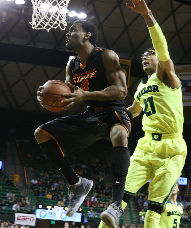 Photo - Oklahoma State forward Brian Williams (4) drives past Baylor center Isaiah Austin (21), right, in the first half of an NCAA college basketball game, Monday, Feb. 17, 2014, in Waco, Texas. (AP Photo/Waco Tribune Herald, Rod Aydelotte)