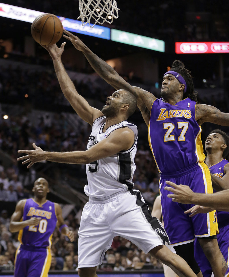 Photo - San Antonio Spurs' Tony Parker (9), of France, is pressured by Los Angeles' Jordan Hill (27) as he drives to the basket during the first half of an NBA basketball game, Wednesday, April 16, 2014, in San Antonio. (AP Photo/Eric Gay)