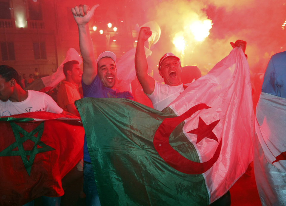 Photo - Algerian soccer fans celebrate with their national flags after their team qualified for the World Cup, in Marseille, southern France, Thursday, June 26, 2014. Algeria drew with Russia 1-1, and advanced to the round of 16 for the first time in their World Cup history. (AP Photo/Claude Paris)