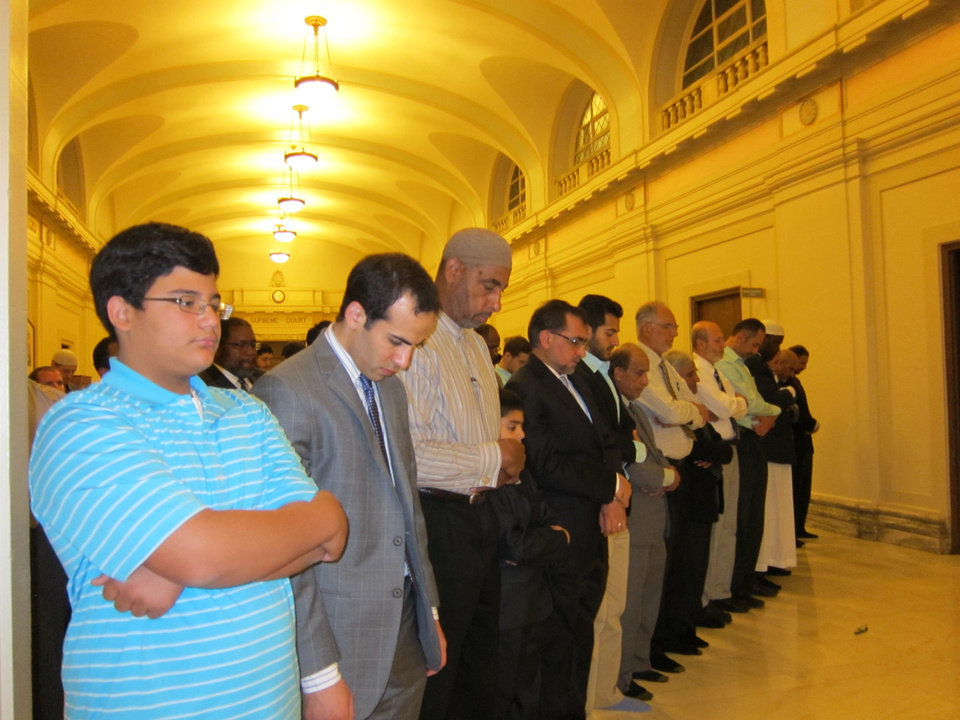 Photo - Muslims pray during an evening prayer held after the Oklahoma State Capitol Interfaith Iftar Dinner Tuesday at the state Capitol. PHOTO BY CARLA HINTON, THE OKLAHOMAN  Carla Hinton - The Oklahoman