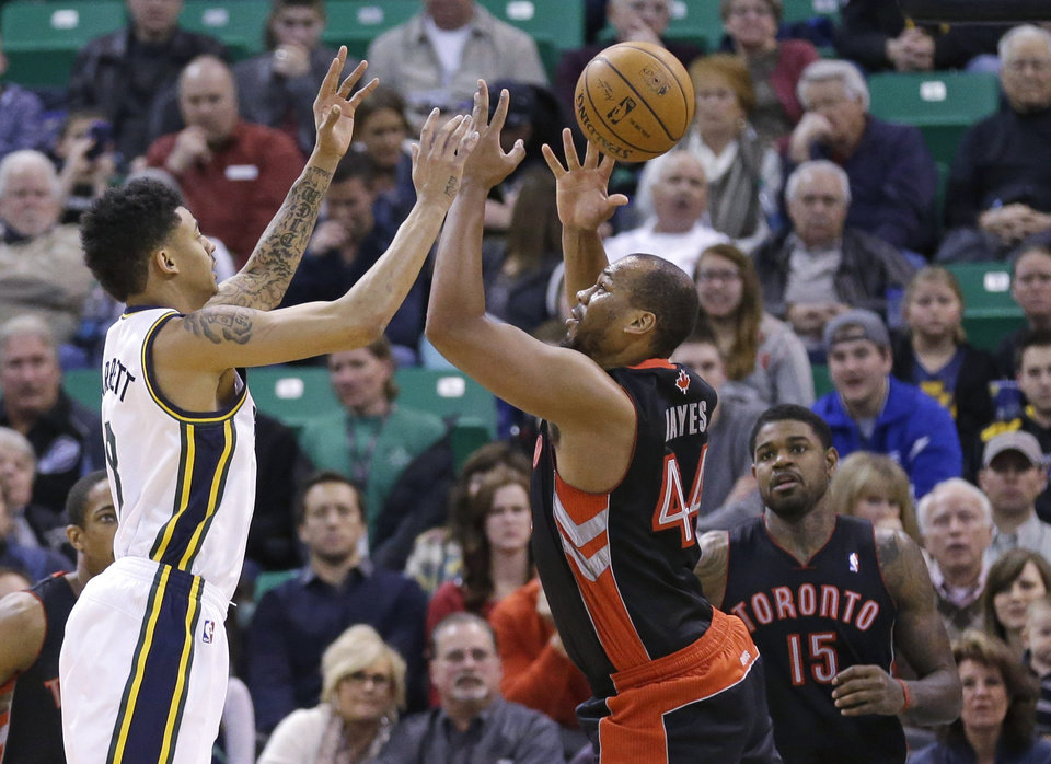 Utah Jazz's Diante Garrett, left, and Toronto Raptors' Chuck Hayes (44) reach for the ball as Toronto Raptors' Amir Johnson (15) looks on in the second quarter of an NBA basketball game, Monday, Feb. 3, 2014, in Salt Lake City.  (AP Photo/Rick Bowmer)
