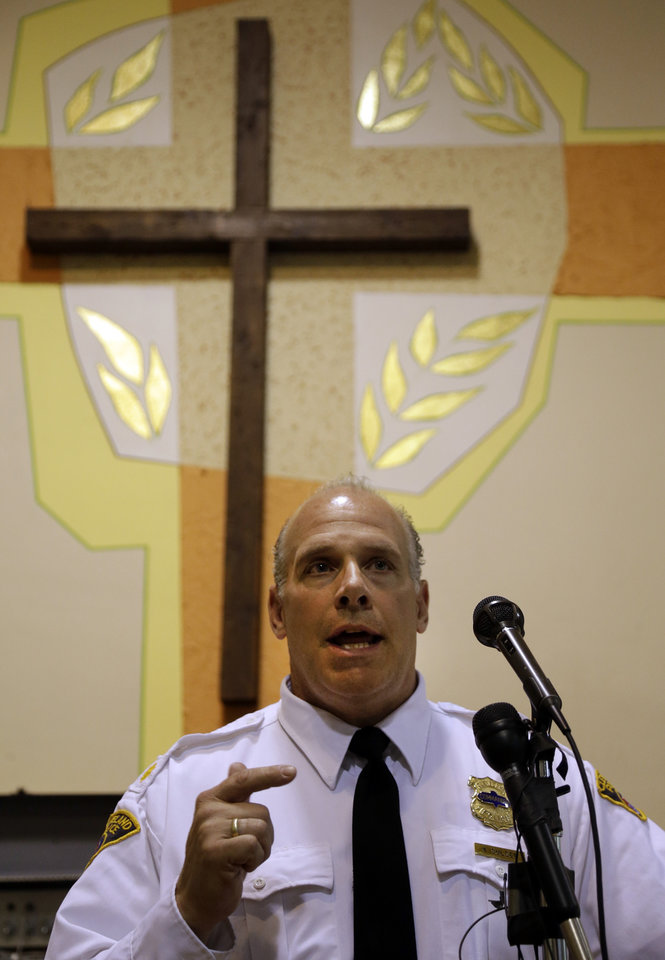 Photo - City of Cleveland Police Commander Kieth Sulzer speaks during a community meeting in the neighborhood near the crime scene where three women were found in Cleveland, Ohio, Thursday, May 9, 2013. Prosecutors said Thursday they may seek the death penalty against Ariel Castro, the man accused of imprisoning three women at his home for a decade, as police charged that he impregnated one of his captives at least five times and made her miscarry by starving her and punching her in the belly. (AP Photo/David Duprey)