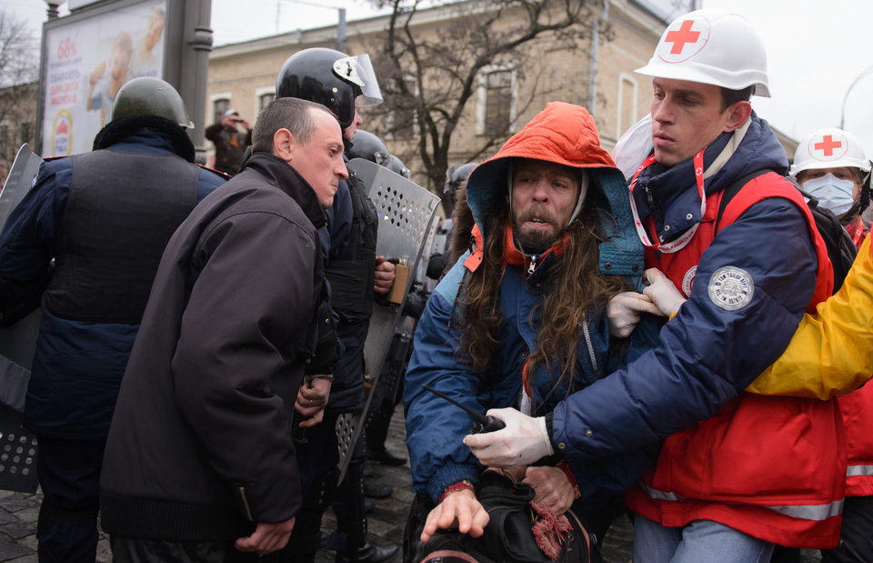 Photo - Medical workers lead away a pro-Western activist after clashes with pro-Russia activists in Kharkiv, Ukraine, Sunday, April 13, 2014. Two rival rallies in Kharkiv turned violent after a group of pro-Russian protesters followed several pro-Ukrainian activists, beating them with baseball bats and sticks. (AP Photo/ Olga Ivashchenko)