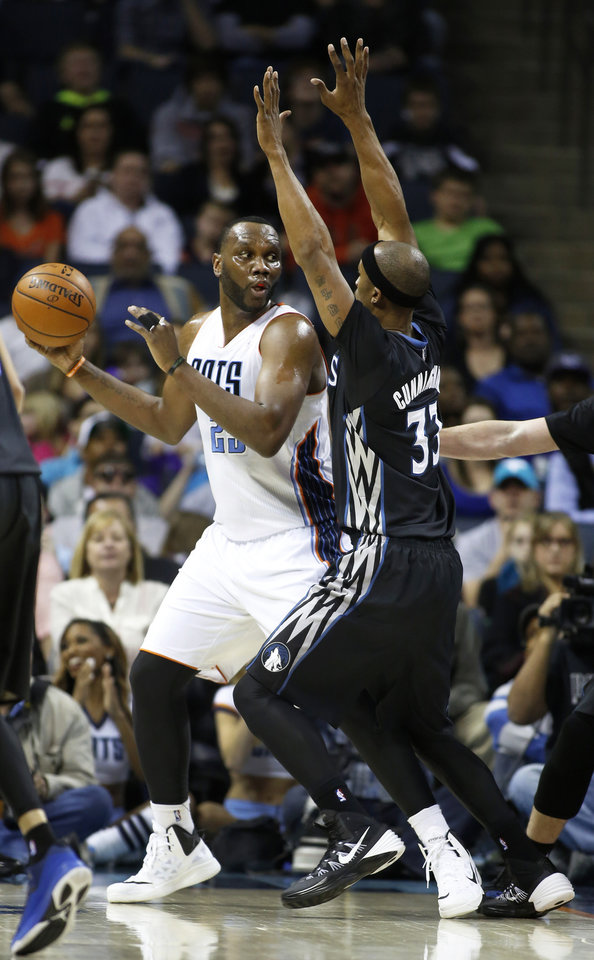 Photo - Charlotte Bobcats center Al Jefferson, left, tries to pass around Minnesota Timberwolves forward Dante Cunningham during the first half of an NBA basketball game in Charlotte, N.C., Friday, March 14, 2014. (AP Photo/Nell Redmond)
