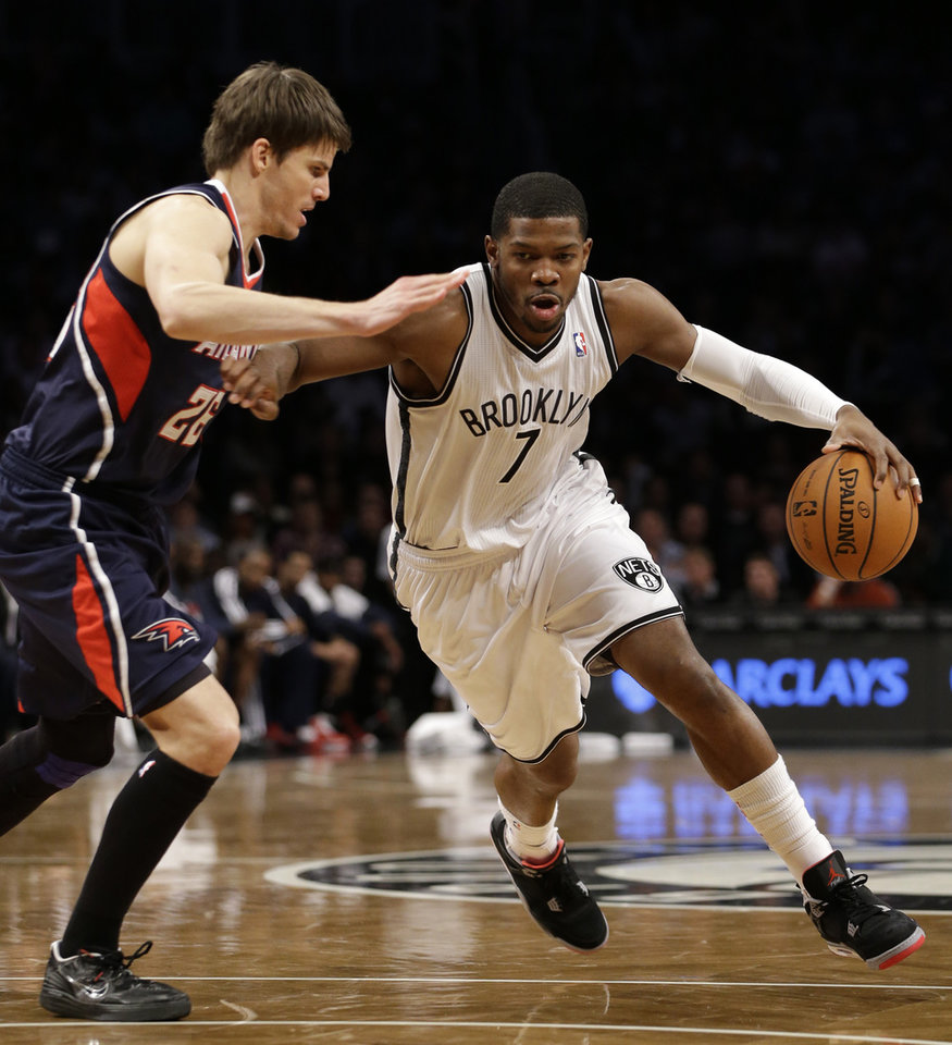 Brooklyn Nets guard Joe Johnson (7) drives past Atlanta Hawks guard Kyle Korver (26) in the first half of their NBA basketball game at the Barclays Center, Friday, Jan. 18, 2013, in New York. (AP Photo/Kathy Willens)