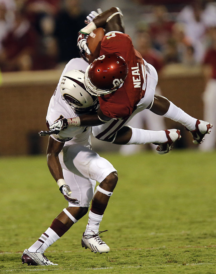 Photo - Oklahoma's Durron Neal (5) is upended by Louisiana Monroe's Vincent Eddie (14) during the college football game between the University of Oklahoma Sooners (OU) and the University of Louisiana Monroe Warhawks (ULM) at the Gaylord Family Memorial Stadium on Saturday, Aug. 31, 2013 in Norman, Okla.  Photo by Chris Landsberger, The Oklahoman