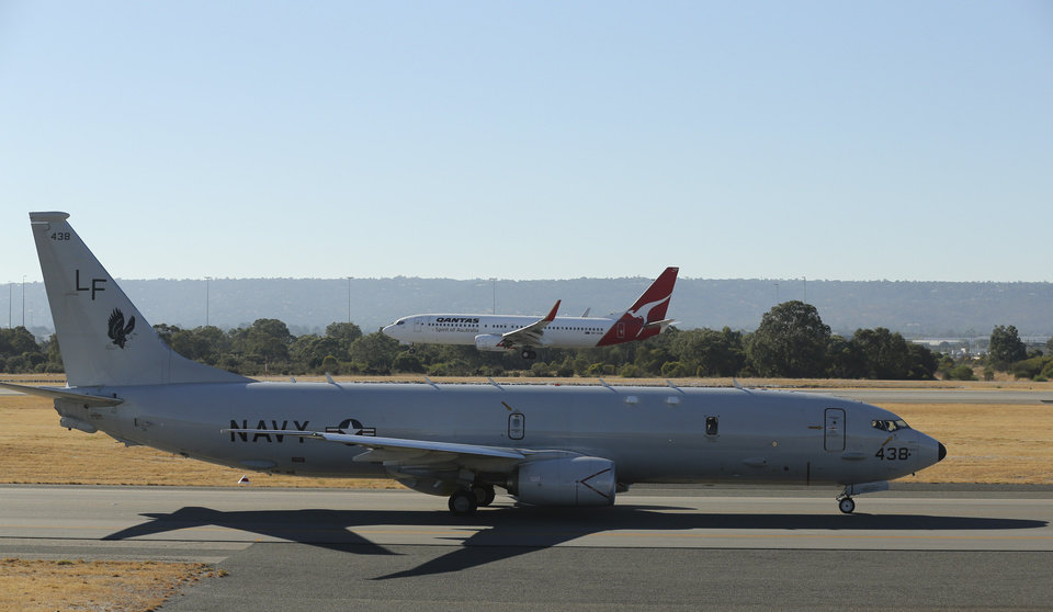 Photo - A Qantas jet lands behind a U.S. Navy P-8 Poseidon as it taxies along the runway at Perth Airport en route to rejoin the ongoing search operations for missing Malaysia Airlines Flight 370 in Perth, Australia, Friday, April 11, 2014. An air and sea hunt for the missing Malaysian jet resumed Friday in the same swath of the southern Indian Ocean where an underwater sensor made the fifth detection of a signal in recent days, raising hopes that searchers are closing in on what could be a flight recorder. (AP Photo/Rob Griffith)