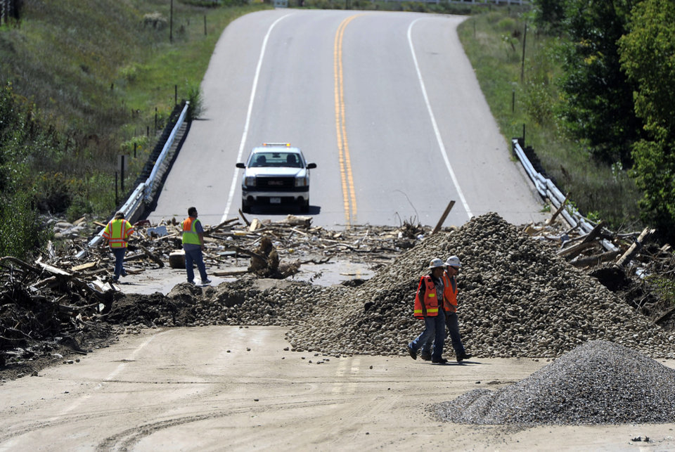 Photo - FILE- In this Sept. 18, 2013, file photo, workers walk by a damaged bridge on Highway 34 over the Big Thompson River near Loveland, Colo., on Wednesday, Sept. 18, 2013. Colorado transportation officials are scrambling to replace key mountain highways with at least gravel before the first winter storms hit as early as October, but rebuilding every flood-damaged road and bridge in the mountains and plains will have to wait until 2014 _ or beyond. (AP Photo/Chris Schneider, File)