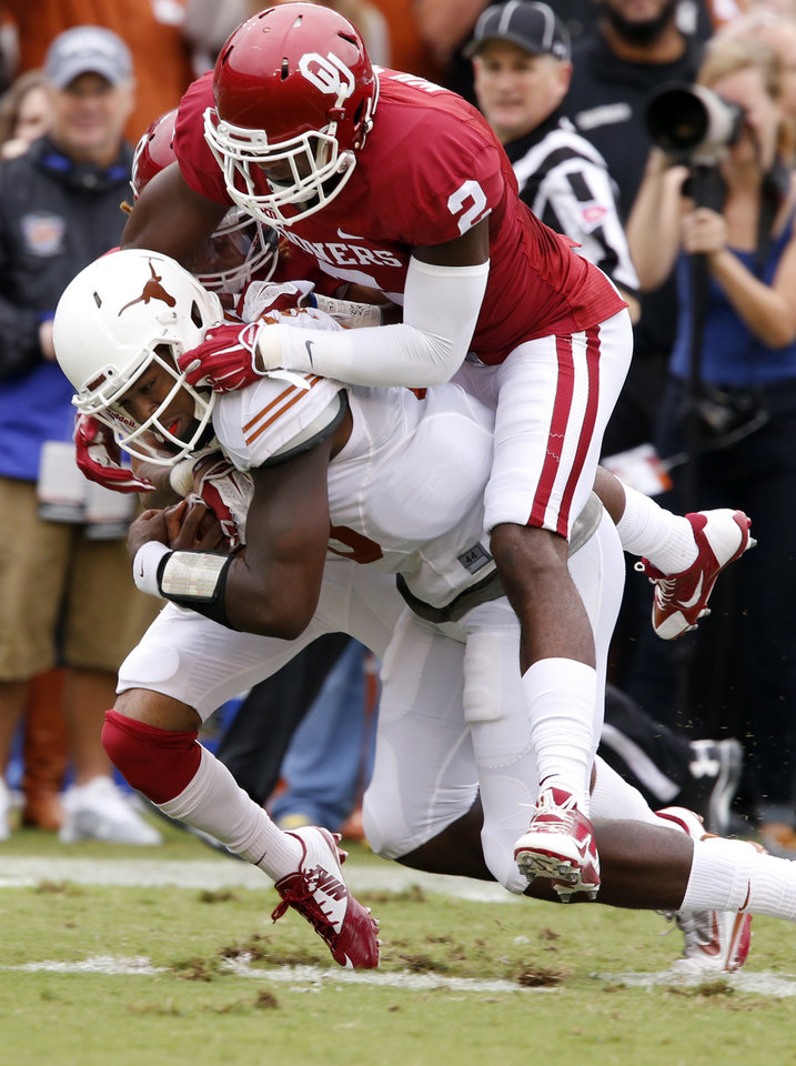 Photo - Oklahoma's Julian Wilson (2) brings down Texas' Tyrone Swoopes (18) after a long run during the Red River Showdown college football game between the University of Oklahoma Sooners (OU) and the University of Texas Longhorns (UT) at the Cotton Bowl in Dallas, Texas on Saturday, Oct. 11, 2014. 