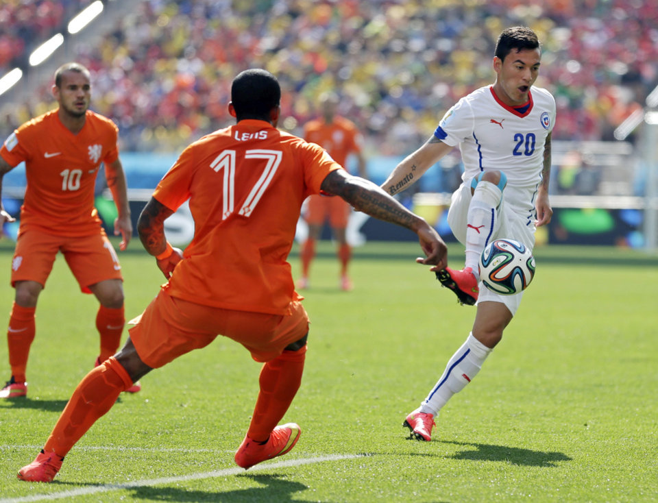 Photo - Chile's Charles Aranguiz stops a pass in front of Netherlands' Jeremain Lens during the group B World Cup soccer match between the Netherlands and Chile at the Itaquerao Stadium in Sao Paulo, Brazil, Monday, June 23, 2014. (AP Photo/Felipe Dana)