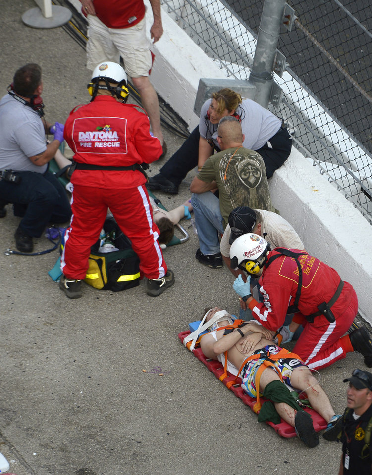 Photo - Emergency personnel attend to injured spectators in front of the grandstands after Kyle Larson's car hit the safety wall and fence along the front stretch on the final lap of the NASCAR Nationwide Series auto race at Daytona International Speedway in Daytona Beach, Fla., Saturday, Feb. 23, 2013. (AP Photo/Phelan M. Ebenhack)