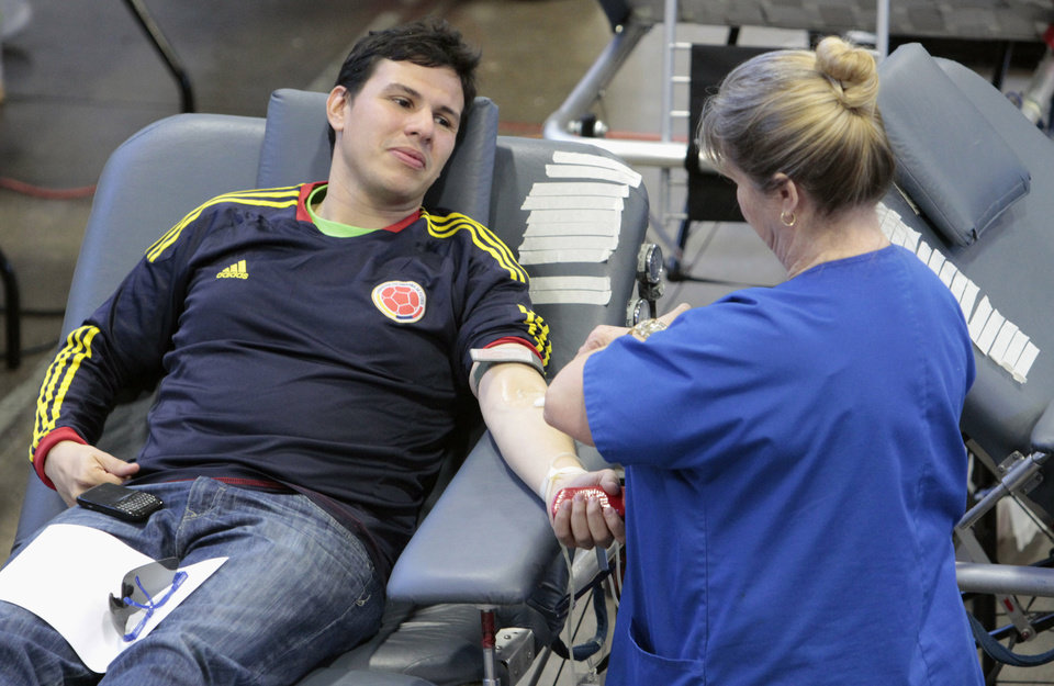 First-time blood donor Sergio Mendez, graduate student from Colombia, listens to Carolyn Patterson with the Oklahoma Blood Institute during the Bedlam Blood Drive at the ROTC armory on the University of Oklahoma campus (OU) on Tuesday, Feb. 21, 2012, in Norman, Okla.  Photo by Steve Sisney, The Oklahoman