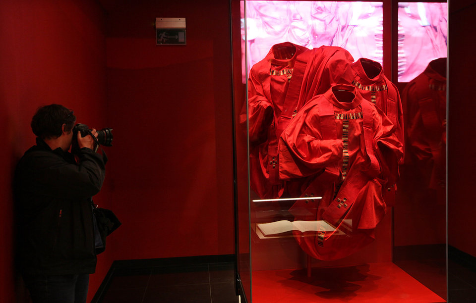 Photo - Original robes that cardinals wore during the 2005 funeral of Pope John Paul II at the Vatican and a copy of the Book of Gospels that the wind closed during that ceremony, are on display at the new multimedia museum to the pope that will open this week at his birth house in Wadowice, Poland, on Monday, April 7, 2014. John Paul II is to be made a saint during a Vatican ceremony, led by Pope Francis  on April 27. (AP Photo/Czarek Sokolowski)