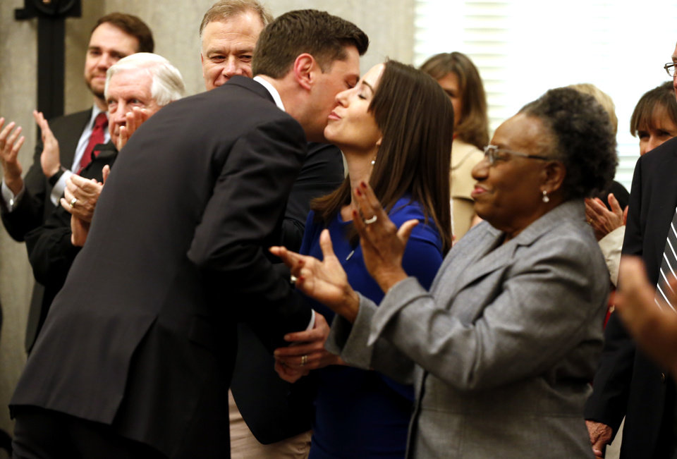 Photo - Mayor David Holt gets a kiss from his wife Rachel after being administered the oath of office as the city's 36th mayor on Tuesday, April 10, 2018 in Oklahoma City, Okla.  Photo by Steve Sisney, The Oklahoman