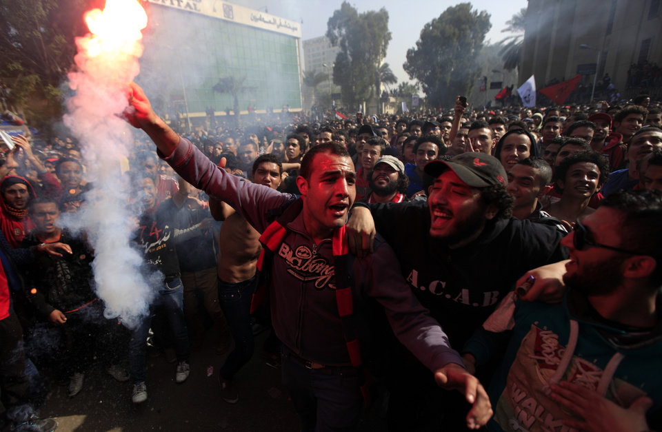 UPDATES DEATH TOLL - Egyptian soccer fans of Al-Ahly club celebrate a court verdict that returned 21 death penalties in last years soccer violence, which left 74 dead, inside the club premises in Cairo, Egypt, Saturday, Jan. 26, 2013. Egyptian security officials say military to deploy in Port Said after 38 people including a senior police officer and a policeman were shot dead in the Mediterranean city of Port Said after a judge sentenced 21 people to death in connection to one of the world's deadliest incidents of soccer violence. (AP Photo/Khalil Hamra)