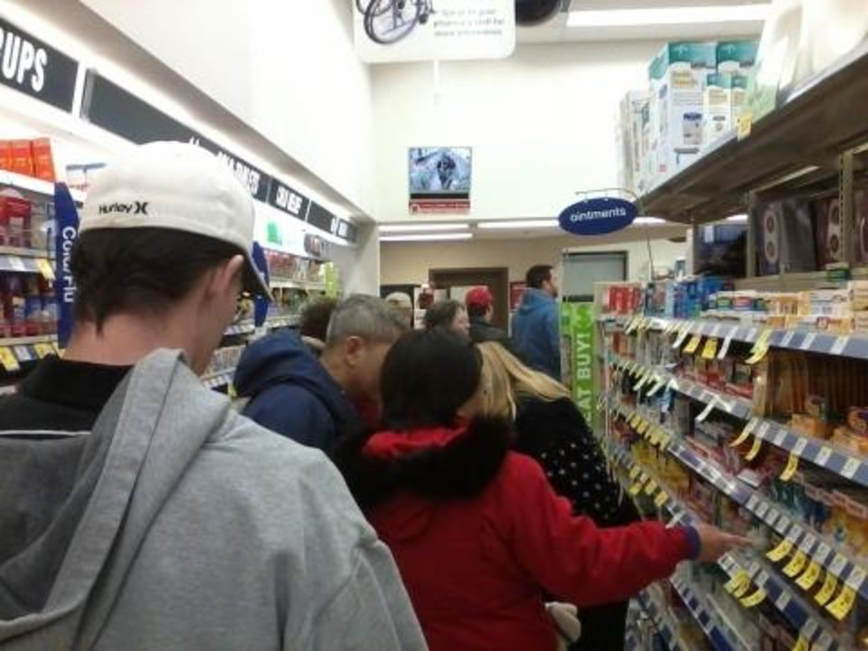 More than two dozen people waited on line at the Walgreens at 2nd Street and Santa Fe in Edmond about 6 p.m. Tuesday in anticipation of yet another major winter storm. A pharmacy technician at the store reported lines crowds Tuesday were even bigger than they were before last week's winter storm. Photo by Steve Lackmeyer