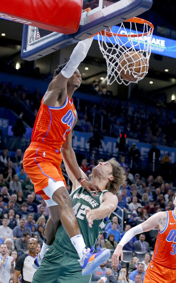 Photo - Oklahoma City's Hamidou Diallo (6) dunks over Milwaukee's Robin Lopez (42) during the NBA game between the Oklahoma City Thunder and the Milwaukee Bucks at Chesapeake Energy Arena,   Sunday, Nov. 10, 2019.  [Sarah Phipps/The Oklahoman]