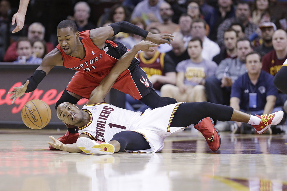 Photo - Cleveland Cavaliers' Jarrett Jack (1) and Toronto Raptors' Terrence Ross (31) battle for a loose ball during the second quarter of an NBA basketball game, Tuesday, Feb. 25, 2014, in Cleveland. (AP Photo/Tony Dejak)