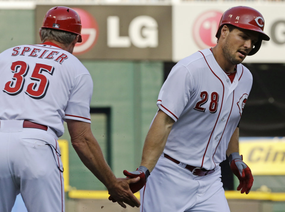 Photo - Cincinnati Reds' Chris Heisey (28) is congratulated by third base coach Chris Speier (35) after Heisey hit a solo home run off Pittsburgh Pirates starting pitcher Francisco Liriano in the first inning of a baseball game, Friday, July 19, 2013, in Cincinnati. (AP Photo/Al Behrman)