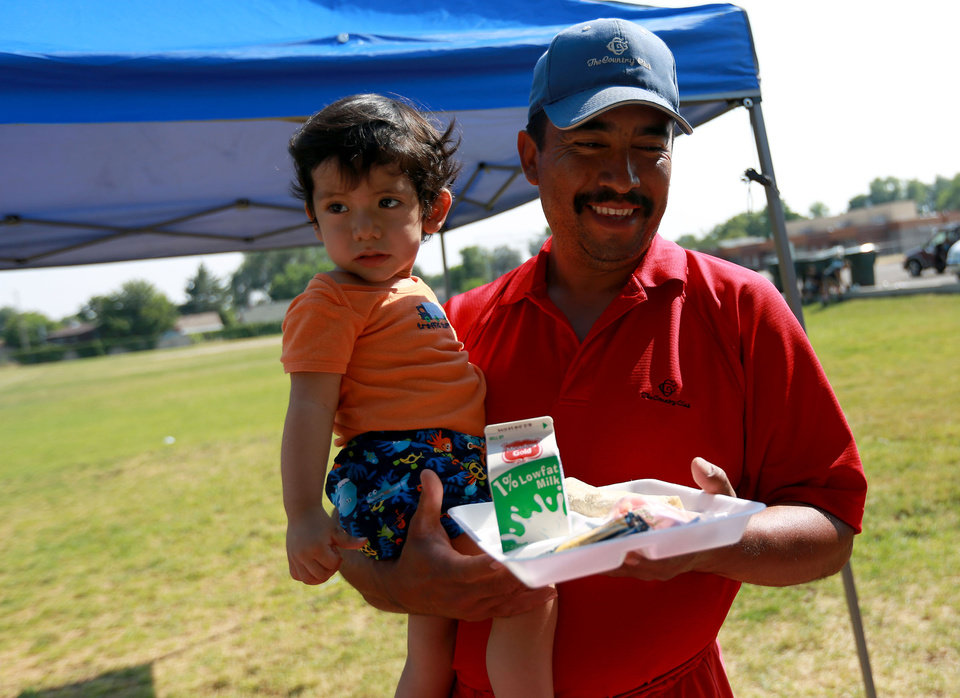 Photo -       Patrick Perez holds his son Emanuel Perez as he gets Emanuel dinner outside of the Central Park Community Center in South Salt Lake on Friday, July 18, 2014. The dinner is part of the Salt Lake CAP summer food program, which offers free dinner to children at five locations in the valley, Monday through Friday.