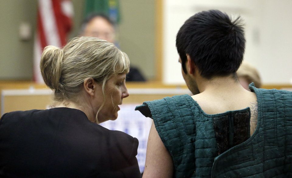 Photo - Defense attorney Ramona Brandes, left, leans across to speak with shooting suspect Aaron Ybarra at a hearing in a King County Jail courtroom Friday, June 6, 2014, in Seattle. Ybarra was arrested in the killing of a 19-year-old student and wounding of two other young people Thursday at Seattle Pacific University. Police say another student pepper-sprayed and tackled him. (AP Photo/Elaine Thompson)