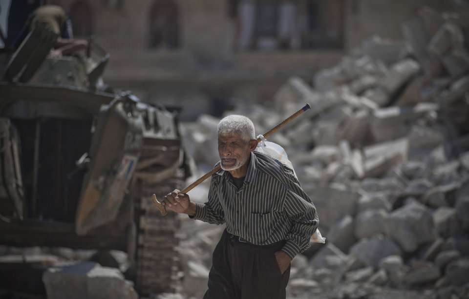 Photo -   In this Wednesday, Aug. 15, 2012 photo, a Syrian elderly man walks past a destroyed building in the town of Azaz on the outskirts of Aleppo, Syria. Thousands of Syrians who have been displaced by the country's civil are struggling to find safe shelter while shelling and airstrikes by government forces continue. (AP Photo/ Khalil Hamra)