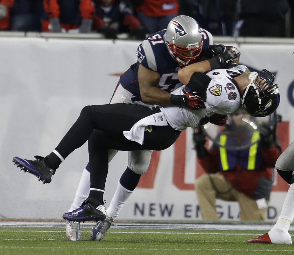 Photo - Baltimore Ravens tight end Dennis Pitta (88) is tackled by New England Patriots outside linebacker Jerod Mayo (51) during the second half of the NFL football AFC Championship football game in Foxborough, Mass., Sunday, Jan. 20, 2013. (AP Photo/Elise Amendola)