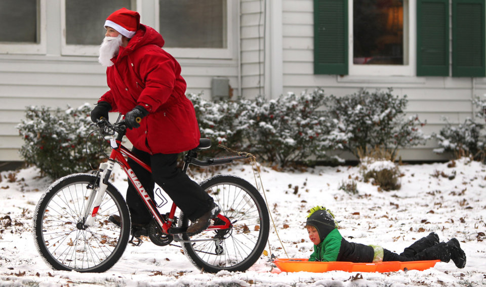 Sam Getz, dressed like Santa Claus, pulls his brother Jacob through the snow on Portland Terrace in Webster Groves, near St. Louis, Mo., on Friday, Dec. 6, 2013.  Though schools were open in on Friday, Sam's mother Jennifer Getz allowed her boys to stay home. (AP Photo/St. Louis Post-Dispatch, Rober Cohen)  EDWARDSVILLE INTELLIGENCER OUT; THE ALTON TELEGRAPH OUT