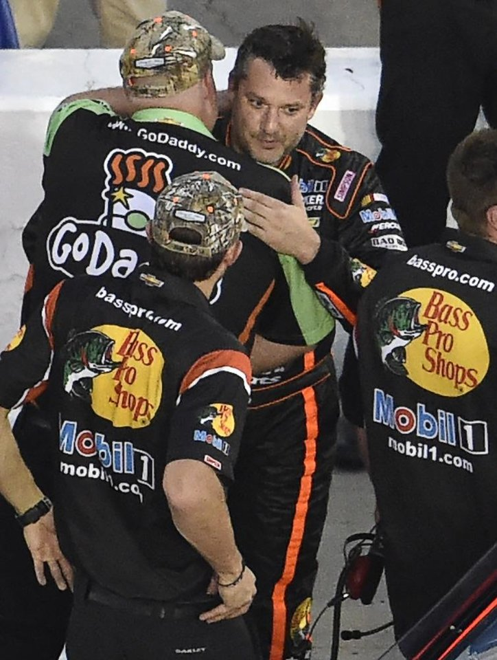 Photo - Sprint Cup Series driver Tony Stewart, right, is congratulated by a crew member for competitor Danica Patrick's Go Daddy team during qualifying for Sunday's NASCAR Sprint Cup Series auto race at Atlanta Motor Speedway, Friday, Aug. 29, 2014 in Hampton, Ga. (AP Photo/David Tulis)