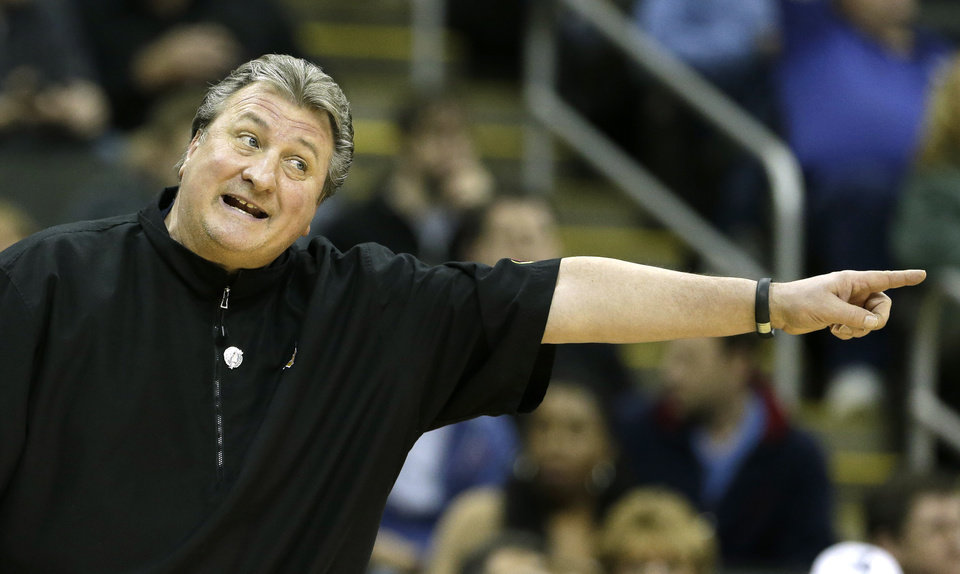 Photo - West Virginia coach Bob Huggins motions to his players during the first half of an NCAA college basketball game against Texas in the Big 12 men's tournament on Thursday, March 13, 2014, in Kansas City, Mo. (AP Photo/Charlie Riedel)