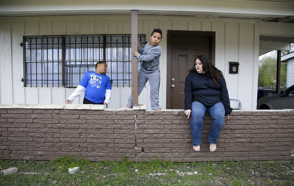 Photo -  Desha Bailey tries to pose her sons for a portrait in front of their home in Tulsa. Bailey regained custody of her two sons after battling and recovering from a drug addiction. The boys were placed in foster care in Sapulpa after Bailey was arrested and placed in drug treatment. [Photo by Jessie Wardarski, Tulsa World]