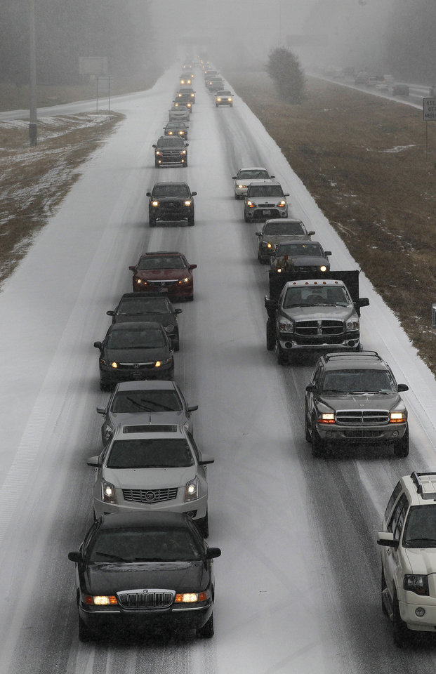 Photo - Vehicles moves slowly on Interstate 575 in North West Ga., Tuesday, Jan. 28, 2014, near Kennesaw, Ga. Georgians stocked up on ice-melting chemicals, school systems closed, and road crews prepared to clear snow and ice from highways as a winter storm took aim. (AP Photo/Mike Stewart)