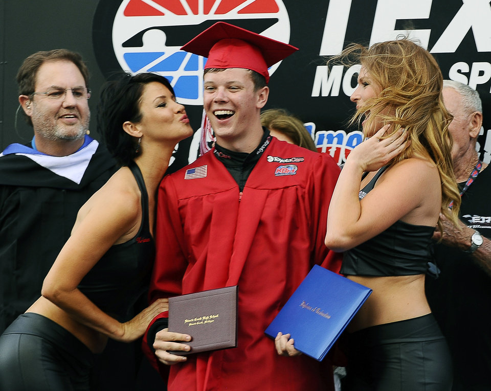 Photo - Erik Jones, center, takes part in a graduation ceremony on the stage during driver introductions for a NASCAR truck race at Texas Motor Speedway in Fort Worth, Texas, Friday, June 6, 2014. Tonight's race falls on the same day as Jone's high school senior graduation however, he chose to forego the opportunity to walk across the stage with his fellow classmates to drive in the race. (AP Photo/Ralph Lauer)