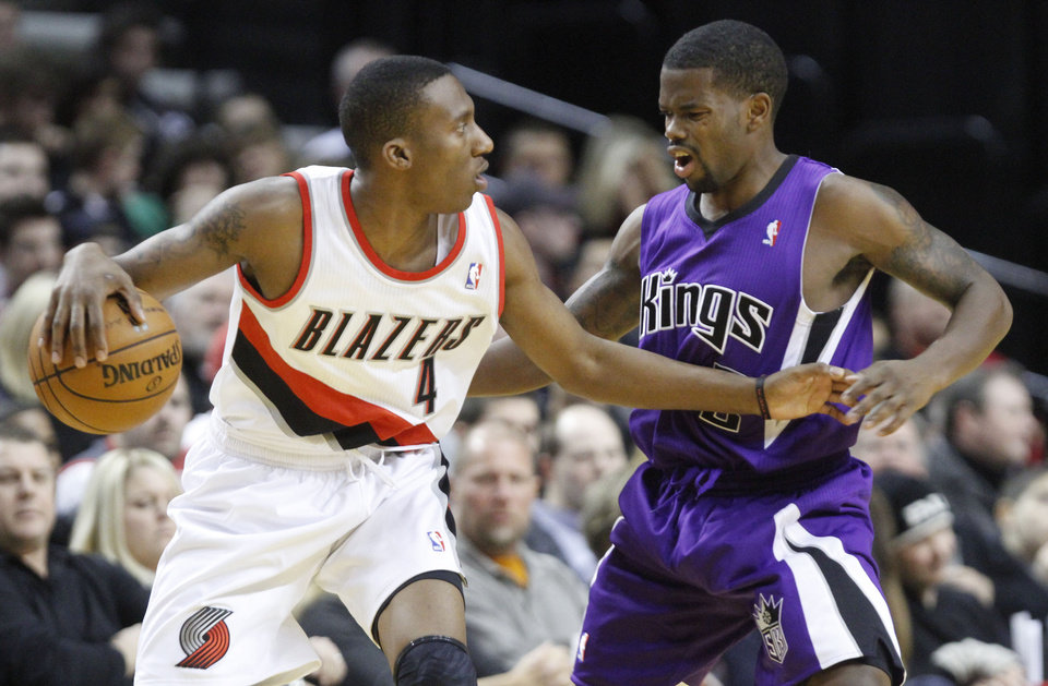 Portland Trail Blazers guard Nolan Smith, left, dribbles on Sacramento Kings guard Aaron Brooks during the first quarter of their NBA basketball game in Portland, Ore., Saturday, Dec. 8, 2012.(AP Photo/Don Ryan)