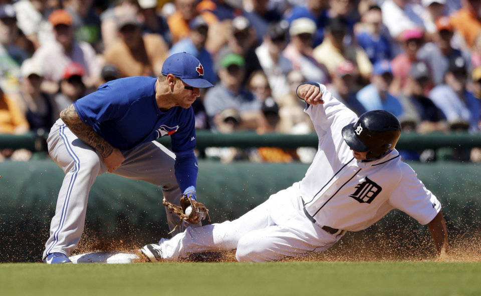 Photo - Toronto Blue Jays third baseman Brett Lawrie tags out Detroit Tigers runner Ben Guez, right, on an attempted steal during the third inning of a spring exhibition baseball game in Lakeland, Fla., Tuesday, March 18, 2014. (AP Photo/Carlos Osorio)