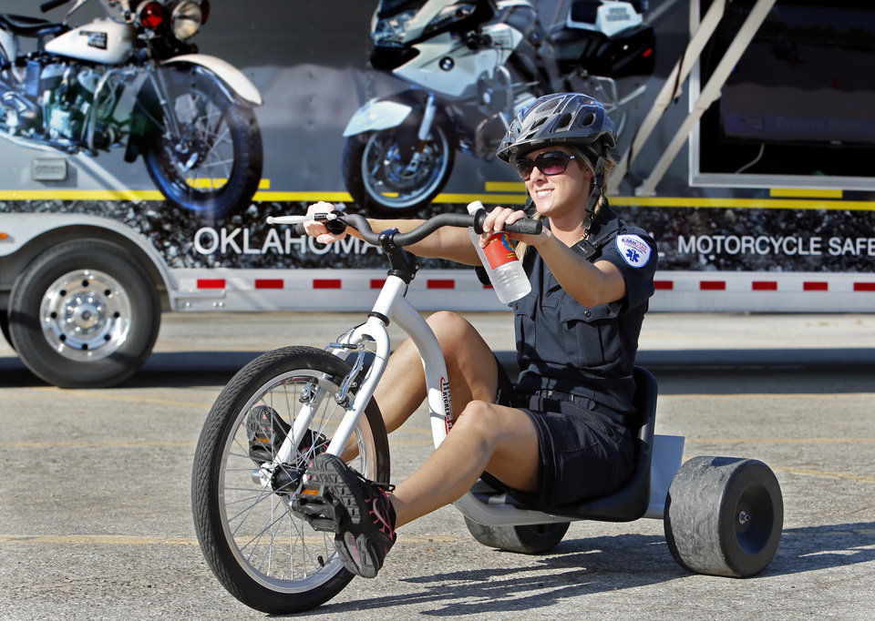 Photo -  Paramedic Melissa Denison rides past an Oklahoma Highway Patrol vehicle display as she and other public safety officials give a demonstration ride for children about to participate in The Ride, a big-wheel race in Norman on Saturday benefiting United Way. PHOTO BY STEVE SISNEY, THE OKLAHOMAN   STEVE SISNEY -