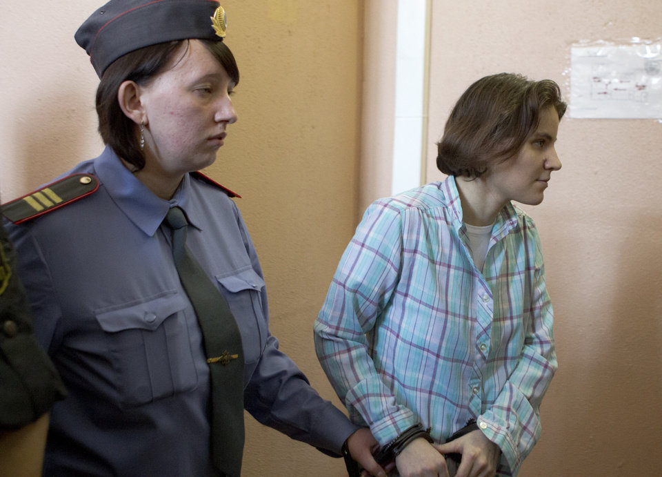 Photo -   Yekaterina Samutsevich, right, a member of feminist punk group Pussy Riot is excorted to a court room in Moscow, Russia, Friday, Aug. 17, 2012. Security is tight around a Moscow courthouse where three members of the feminist punk band Pussy Riot are to hear the verdict Friday in a trial that could send them to prison for seven years. (AP Photo/Misha Japaridze)