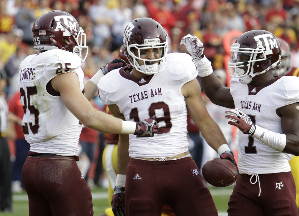 Texas A&M tight end Michael Lamothe, center, celebrates with teammates Ryan Swope, left, and Uzoma Nwachukwu after catching a touchdown pass during the first half of an NCAA college football game against Iowa State, Saturday, Oct. 22, 2011, in Ames, Iowa. (AP Photo/Charlie Neibergall) ORG XMIT: IACN103