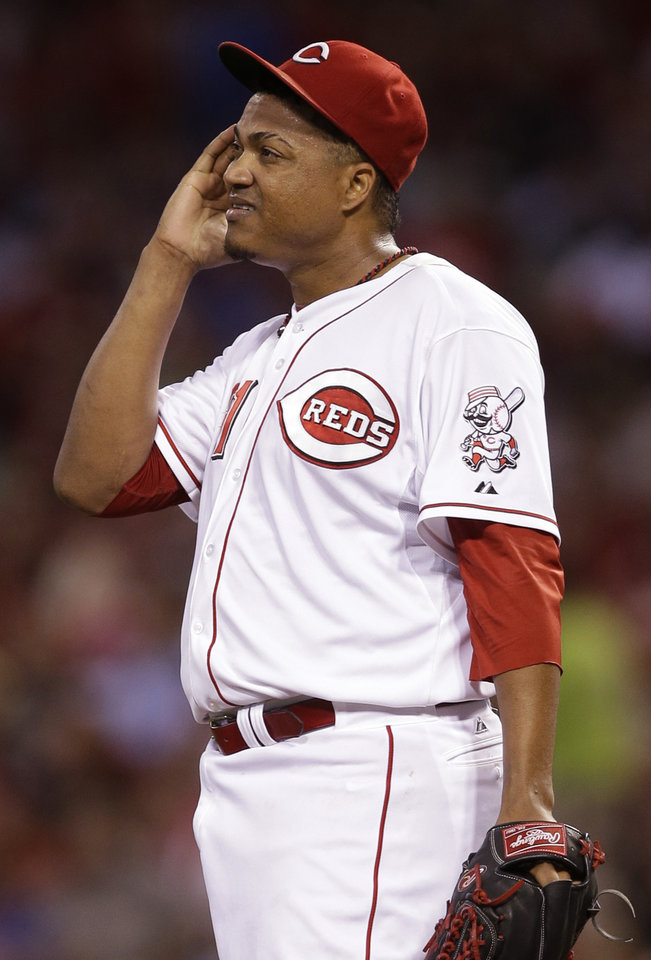 Photo - Cincinnati Reds starting pitcher Alfredo Simon wipes his face in the seventh inning of a baseball game against the Chicago Cubs, Wednesday, July 9, 2014, in Cincinnati. Simon pitched six and two-thirds innings, giving up one run, in winning his 12th game of the season 4-1. (AP Photo/Al Behrman)