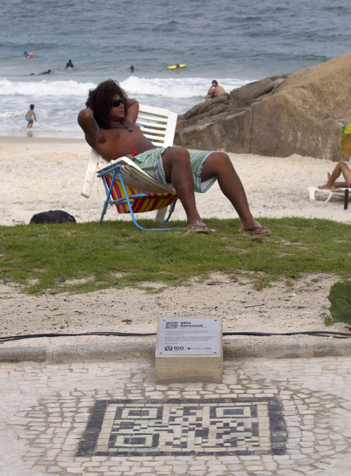 A man rests on a grassy area of the beach near a new QR code made out of the black and white stones on the sidewalk in Rio de Janeiro, Brazil, Friday, Jan. 25, 2013.  The QR codes are being placed at tourist spots which can be scanned with a mobile device for information about the site. (AP Photo/Silvia Izquierdo)