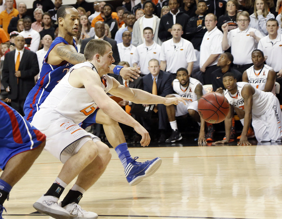 Kansas' Travis Releford (24) and Oklahoma State 's Phil Forte (13) battle for the loose ball in the final seconds of the game during the college basketball game between the Oklahoma State University Cowboys (OSU) and the University of Kanas Jayhawks (KU) at Gallagher-Iba Arena on Wednesday, Feb. 20, 2013, in Stillwater, Okla. Photo by Chris Landsberger, The Oklahoman