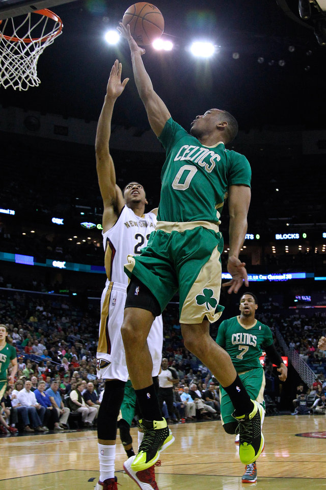 Photo - Boston Celtics guard Avery Bradley (0) drives to the basket against New Orleans Pelicans forward Anthony Davis, left, during the first half of an NBA basketball game in New Orleans, Sunday, March 16, 2014. (AP Photo/Jonathan Bachman)