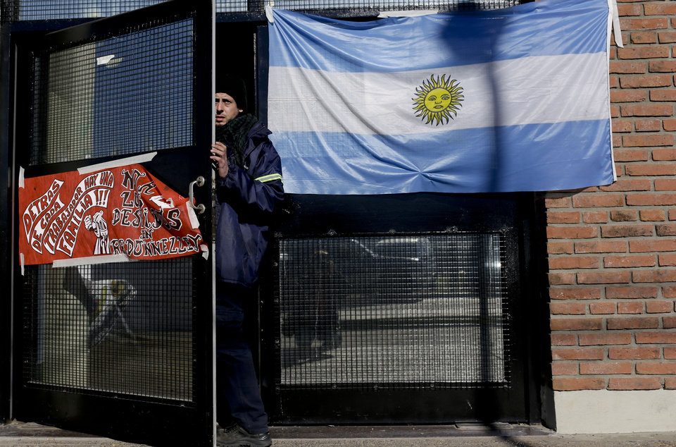 Photo - A worker stands in the doorway of the R.R. Donnelley & Sons printing plant, on the outskirts of Buenos Aires, Argentina, Thursday, Aug. 14, 2014. The global printing company based in the U.S. shuttered its plant Monday amid tough economic times in the South American country. About 200 workers decided to keep working, despite not being paid, until union leaders, in talks with the Labor Ministry, find a solution to reverse the plant layoffs.  (AP Photo/Natacha Pisarenko)