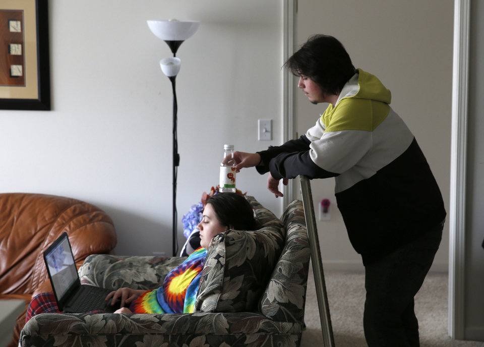Photo - In this Friday, March 21, 2014 photo, Cody Lewis, right, jokes with his sister, Mackenzie, as she surfs the Internet at their suburban Chicago home in Aurora, Ill. Lewis was consumed by heroin. Every day was the same: Get up sick if he hadn't used in 12 hours. Figure out how to get money. Then drive 35 miles from his suburban home to Chicago to score.