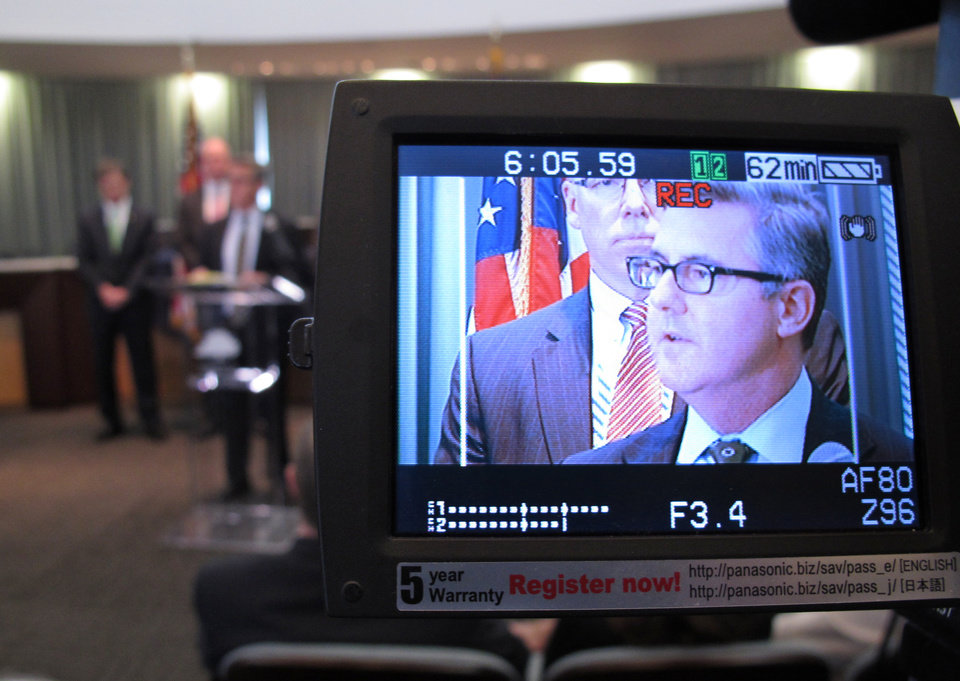 Photo - Assistant U.S. Attorney Thomas Walker, displayed on a video camera monitor, speaks at a news conference at the town hall in  Wake Forest, N.C., on Thursday, April 10, 2014. He was discussing the rescue of kidnapped Wake Forest resident Frank Arnold Janssen in Atlanta, late the previous night.  (AP Photo/Allen G. Breed)