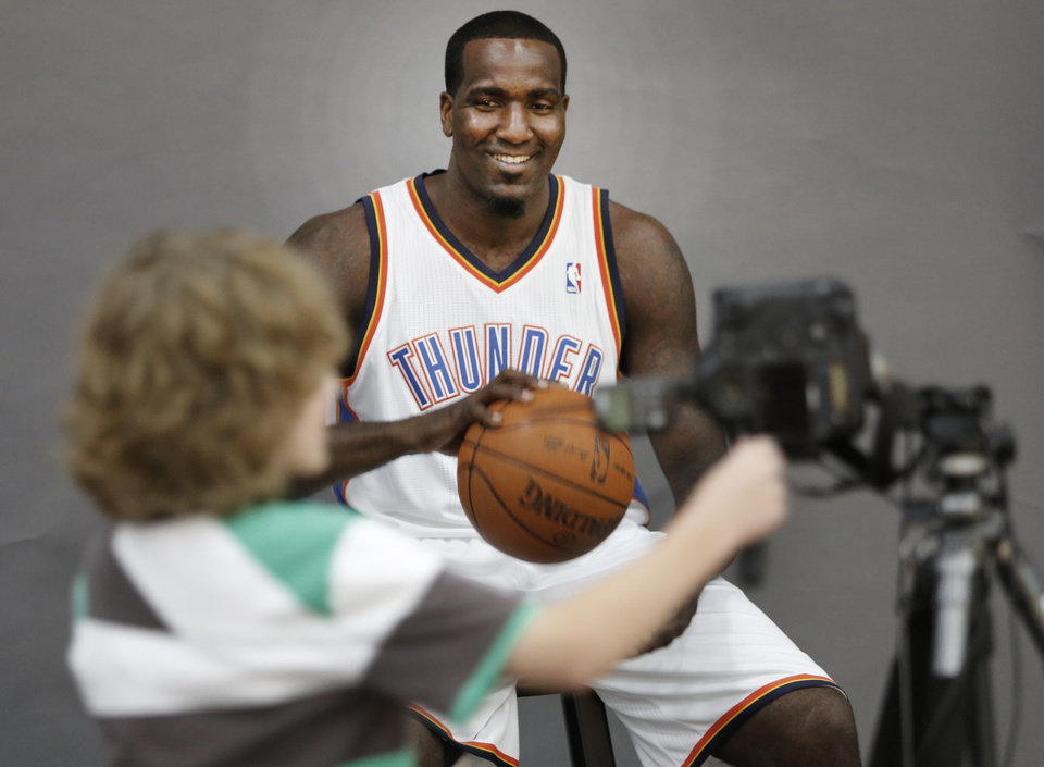 Tabius Landsberger, 11, takes a photo of Kendrick Perkins during media day with the Oklahoma City Thunder in Oklahoma City, Thursday September 27, 2013. Photo By Steve Gooch, The Oklahoman