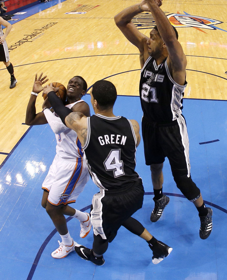 Photo - Oklahoma City's Reggie Jackson (15) hurts his ankle as he runs into San Antonio's Danny Green (4) and Tim Duncan (21) during Game 4 of the Western Conference Finals in the NBA playoffs between the Oklahoma City Thunder and the San Antonio Spurs at Chesapeake Energy Arena in Oklahoma City, Tuesday, May 27, 2014. Photo by Bryan Terry, The Oklahoman